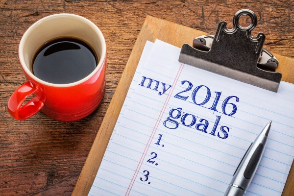 my 2016 goals list on clipboard and coffee against grunge wood desk
